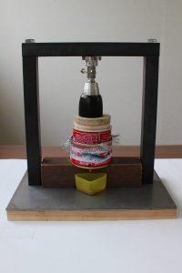 自家製ミニ搾油器で椿油をしぼっている写真