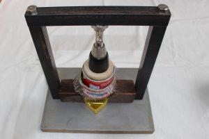 自家製の搾油器で菜種油を搾る写真