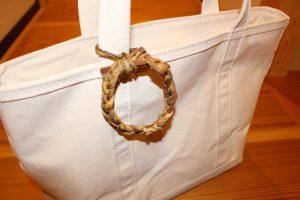 芋茎で作った三つ編みリースをバッグチャームにする写真