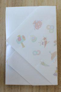 宝尽くしの懐紙にカラスウリの種を包む写真